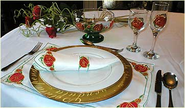 Table set with Mackintosh Rose design glass ware and linen
